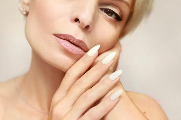 Retrato de uma mulher com uma pele limpa, saudável e uma longa manicure com esmalte de leite close-up.