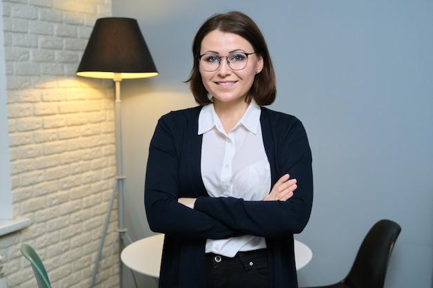 Retrato de uma mulher confiante, psicóloga, psicoterapeuta, assistente social, professora de braços cruzados, olhando para a câmera no escritório