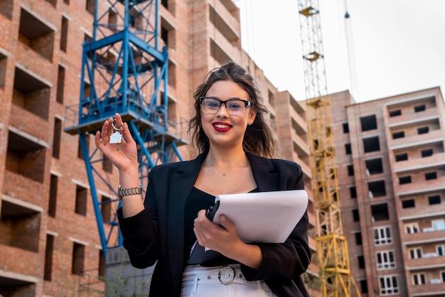 Retrato de uma mulher corretora de imóveis em frente a uma casa nova. conceito de venda ou aluguel