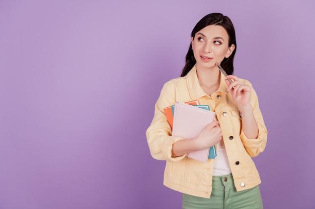 Retrato de uma mulher curiosa e alegre segurando o caderno de pilha olha o espaço em branco no fundo roxo
