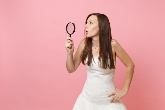Retrato de uma mulher curiosa e chocada em um vestido branco olhando para o lado através de uma lupa