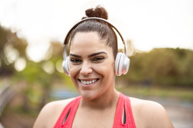 Retrato de uma mulher curvilínea ouvindo uma lista de reprodução de música após uma rotina de corrida ao ar livre - foco no rosto