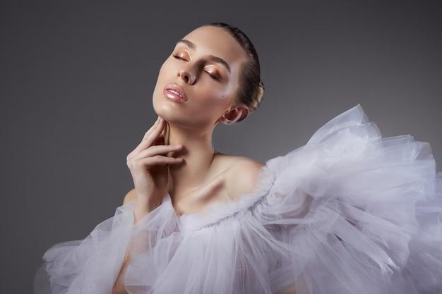 Retrato de uma mulher de beleza romântica em um vestido leve. cosméticos naturais, pele facial linda e lisa, cabelo preso em um coque, corpo artístico