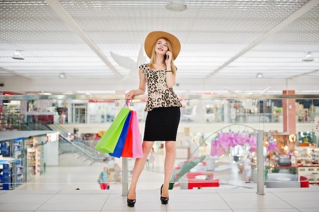 Retrato de uma mulher de blusa de leopardo, saia preta andando no shopping com malas e falando ao telefone.