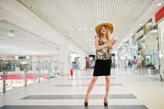 Retrato de uma mulher de blusa de leopardo, saia preta, posando no shopping com chapéu e uma xícara de café.