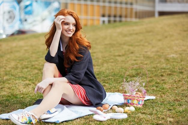 Retrato de uma mulher de cabeça vermelha feliz fazendo piquenique de páscoa
