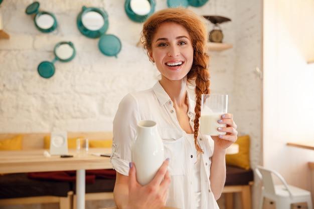 Retrato de uma mulher de cabeça vermelha feliz segurando a garrafa com leite