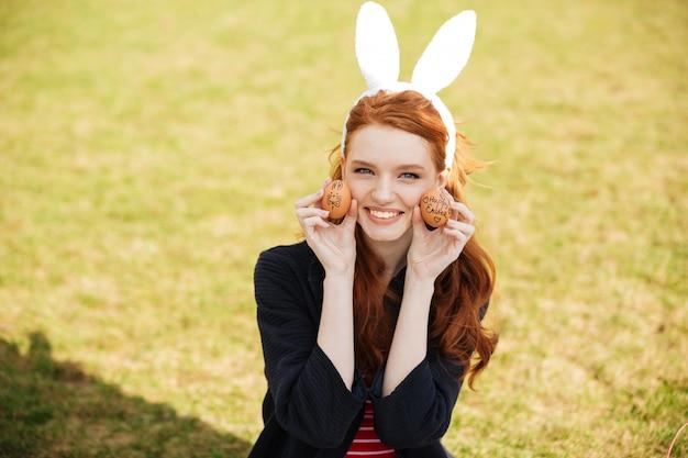 Retrato de uma mulher de cabeça vermelha sorridente usando orelhas de coelho