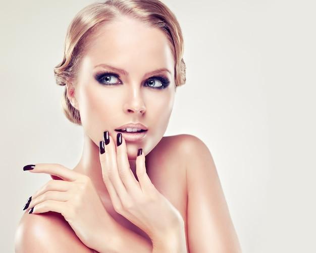 Retrato de uma mulher de cabelo loira com penteado retrô elegante com grande coque de cabelo. unhas compridas nos dedos são manicuradas pela cor preta, maquiagem estilo olhos esfumados em seu rosto. glamour e elegância.