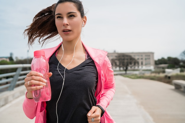 Retrato de uma mulher de fitness correndo ao ar livre na rua. esporte e conceito de estilo de vida saudável.