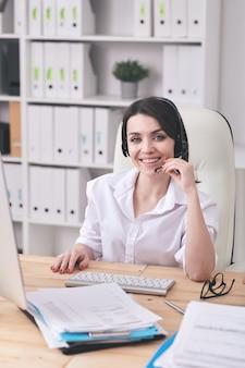 Retrato de uma mulher de helpdesk atraente e alegre ajustando o microfone enquanto fala com o cliente pelo fone de ouvido com microfone sem fio