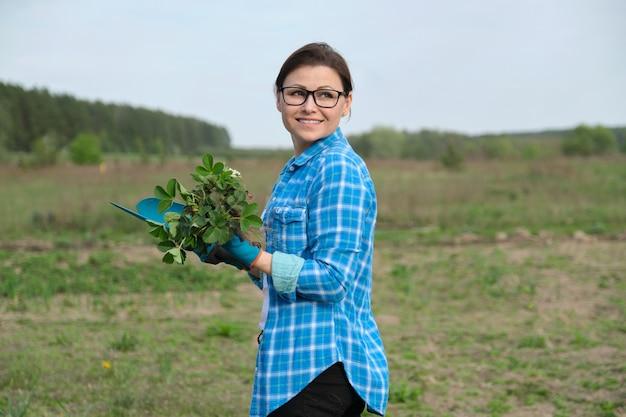 Retrato de uma mulher de meia-idade no jardim com ferramentas, arbustos de morango