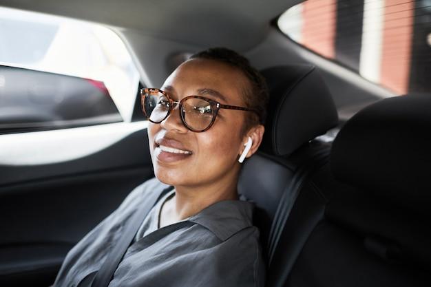 Retrato de uma mulher de negócios africana em óculos, sentada no banco de trás do carro e sorrindo para a câmera