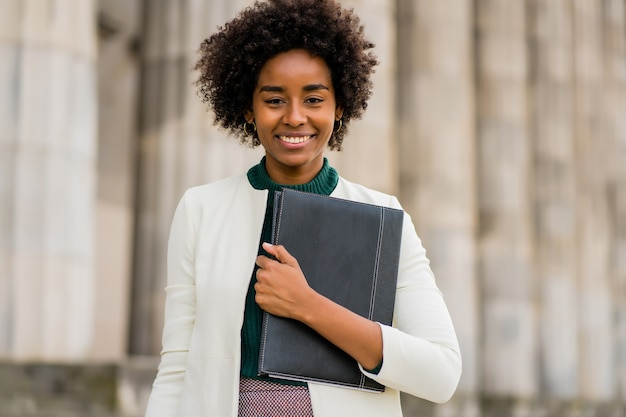 Retrato de uma mulher de negócios afro segurando uma prancheta enquanto fica ao ar livre na rua Foto Premium
