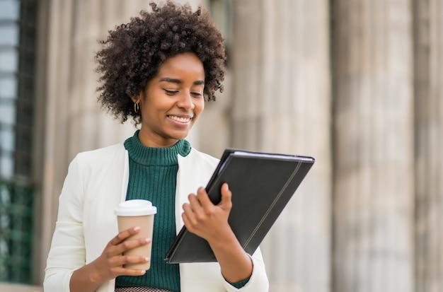 Retrato de uma mulher de negócios afro segurando uma xícara de café e olhando para a área de transferência em pé ao ar livre na rua. negócios e conceito urbano.