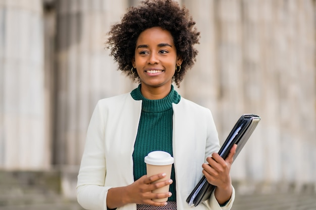 Retrato de uma mulher de negócios afro segurando uma xícara de café e uma prancheta enquanto caminha ao ar livre na rua. negócios e conceito urbano.