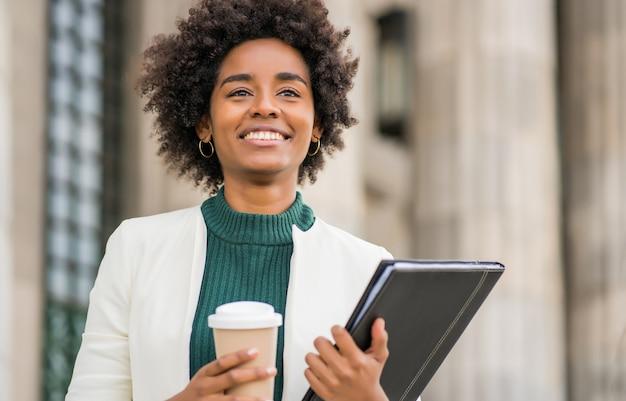 Retrato de uma mulher de negócios afro segurando uma xícara de café e uma prancheta enquanto caminha ao ar livre na rua