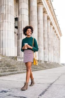 Retrato de uma mulher de negócios afro segurando uma xícara de café enquanto caminha ao ar livre na rua. negócios e conceito urbano.