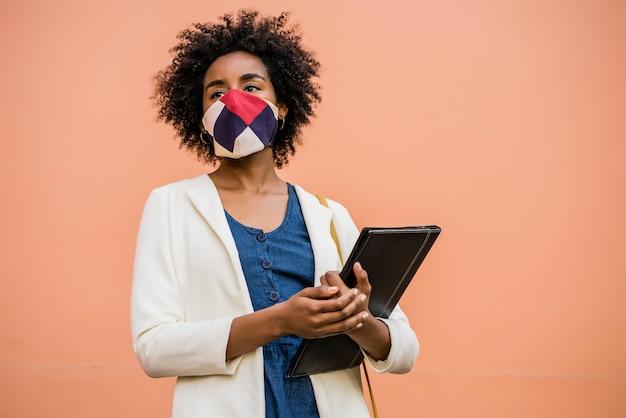 Retrato de uma mulher de negócios afro usando máscara protetora e segurando uma prancheta enquanto fica ao ar livre na rua