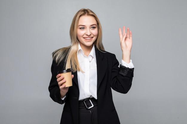 Retrato de uma mulher de negócios alegre que guarda o copo com café.