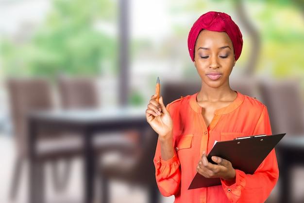Retrato de uma mulher de negócios americano africano jovem atraente com prancheta