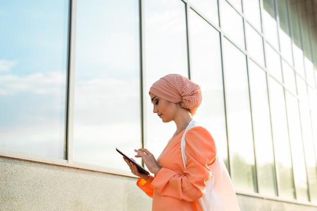 Retrato de uma mulher de negócios árabe em hijab segurando um tablet.