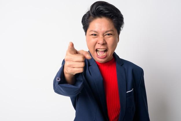 Retrato de uma mulher de negócios asiática e madura vestindo terno contra uma parede branca