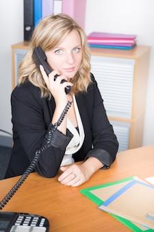 Retrato de uma mulher de negócios atraente jovem usando o telefone no escritório
