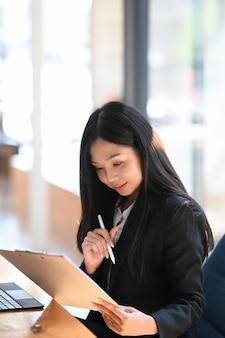 Retrato de uma mulher de negócios atraente, percorrendo informações on-line no tablet digital no escritório moderno.