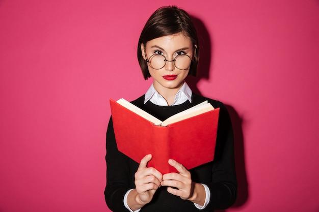 Retrato de uma mulher de negócios atraente sorridente, lendo um livro