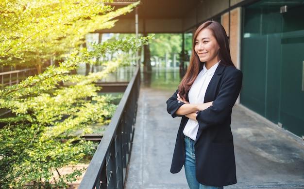 Retrato de uma mulher de negócios bem sucedido asiático em pé no escritório