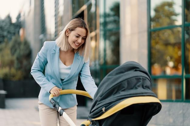 Retrato de uma mulher de negócios bem sucedido em terno azul com bebê