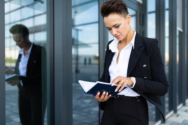 Retrato de uma mulher de negócios bem sucedido no fundo de um arranha-céu