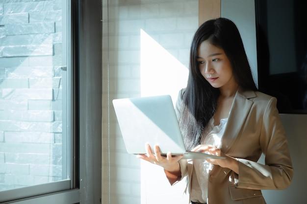 Retrato de uma mulher de negócios bonita que usa o portátil no escritório.