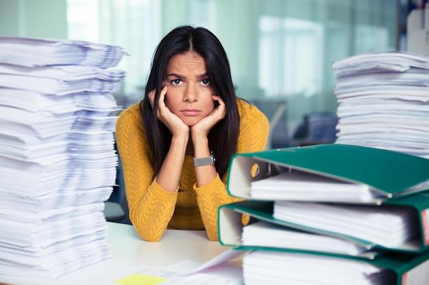 Retrato de uma mulher de negócios casual cansada sentada à mesa no escritório