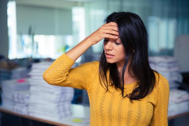 Retrato de uma mulher de negócios casual com dor de cabeça no escritório