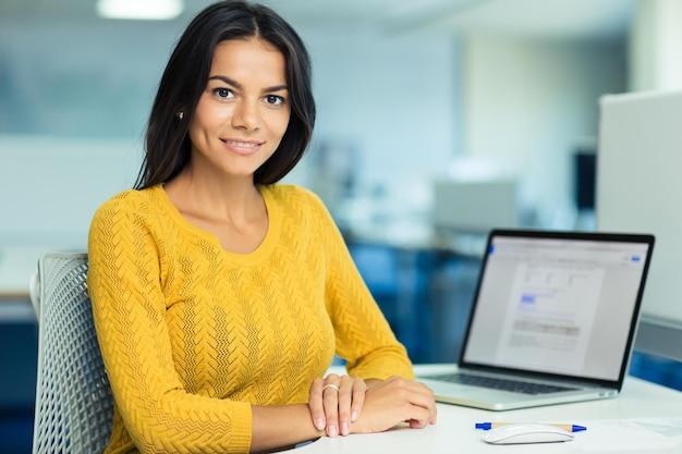 Retrato de uma mulher de negócios casual feliz em suéter sentado em seu local de trabalho no escritório