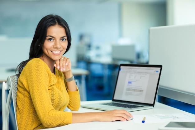 Retrato de uma mulher de negócios casual sorridente, sentada em seu local de trabalho com o laptop no escritório