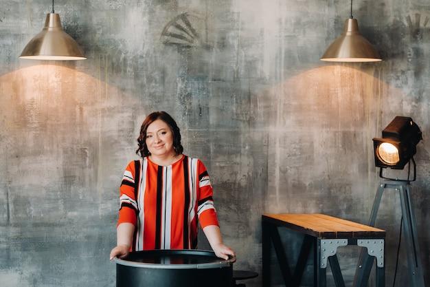 Retrato de uma mulher de negócios com uma jaqueta listrada, sentada em um sofá no interior.