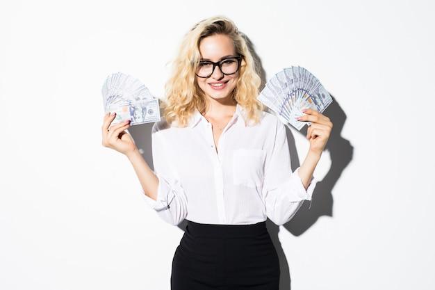Retrato de uma mulher de negócios de terno segurando um monte de notas de dinheiro e comemorando isolado sobre a parede branca