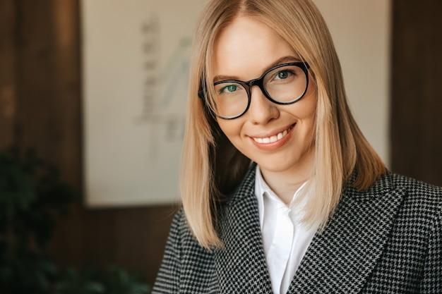 Retrato de uma mulher de negócios em copos, em um terno estrito, sorrindo com os dentes no escritório. trabalhador feliz bem sucedido de escritório.