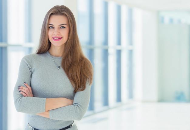 Retrato de uma mulher de negócios em um escritório em um fundo de grandes janelas