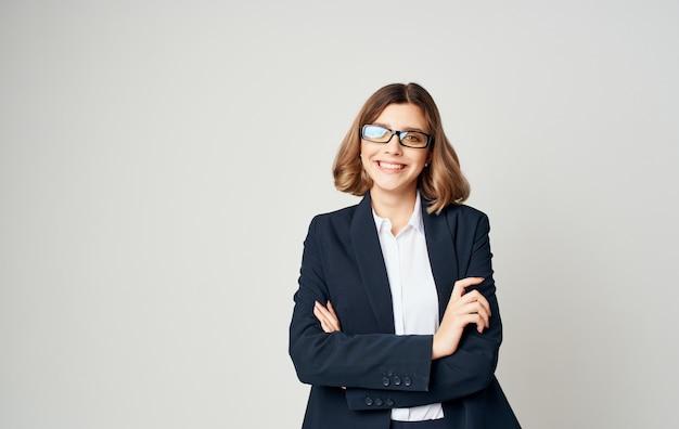 Retrato de uma mulher de negócios em um terno clássico e óculos em um fundo claro