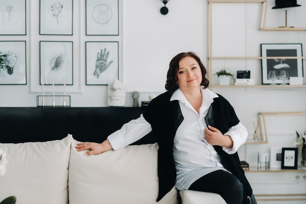 Retrato de uma mulher de negócios em uma camisa branca com um colete sentado em um sofá no interior.