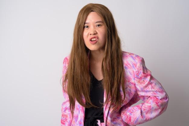 Retrato de uma mulher de negócios esquisita usando terninho rosa e peruca contra uma parede branca