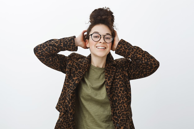 Retrato de uma mulher de negócios europeia confiante e despreocupada com óculos pretos da moda, tocando o cabelo e sorrindo amplamente em pé com um casaco de leopardo sobre uma camiseta casual contra a parede cinza