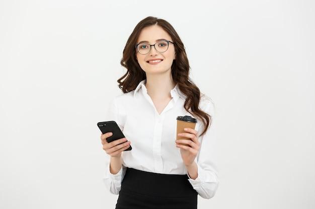 Retrato de uma mulher de negócios feliz e sorridente em óculos segurando uma xícara de café para levar e um telefone celular em pé isolado