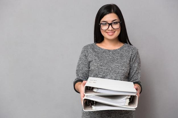 Retrato de uma mulher de negócios feliz segurando pastas na parede cinza