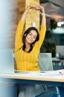 Retrato de uma mulher de negócios feliz sentada à mesa e esticando as mãos no escritório
