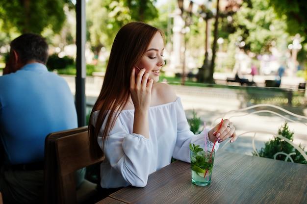 Retrato de uma mulher de negócios jovem atraente segurando um mojito cocktail e falando ao telefone em um café acolhedor ao lado do parque.